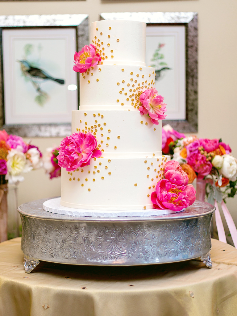 White wedding cake with pink peonies and gold polka dots