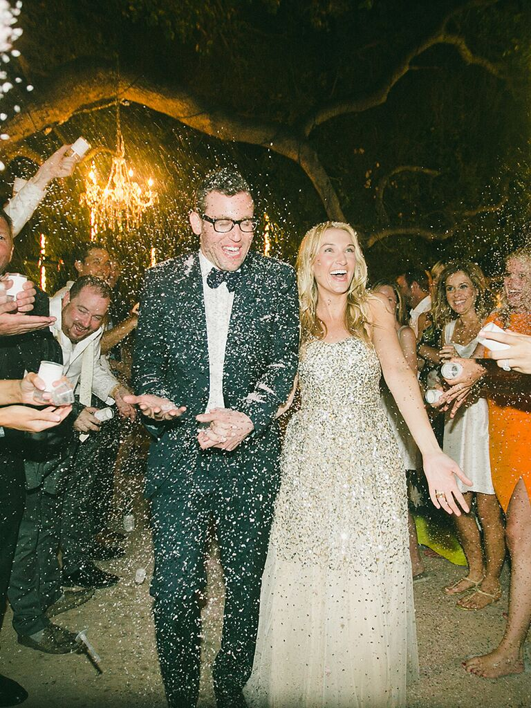 Gold glitter confetti toss over bride and groom