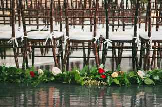 Wedding ceremony seating lined with green garland