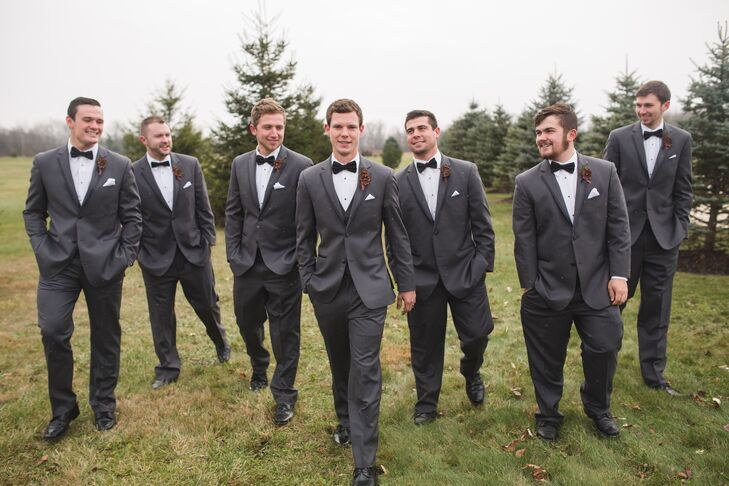 Mason and his groomsmen wore formal charcoal-gray tuxedos with mismatched black bow ties. They all wore pine cone and red berry boutonnieres in keeping with the wintry Christmas theme.
