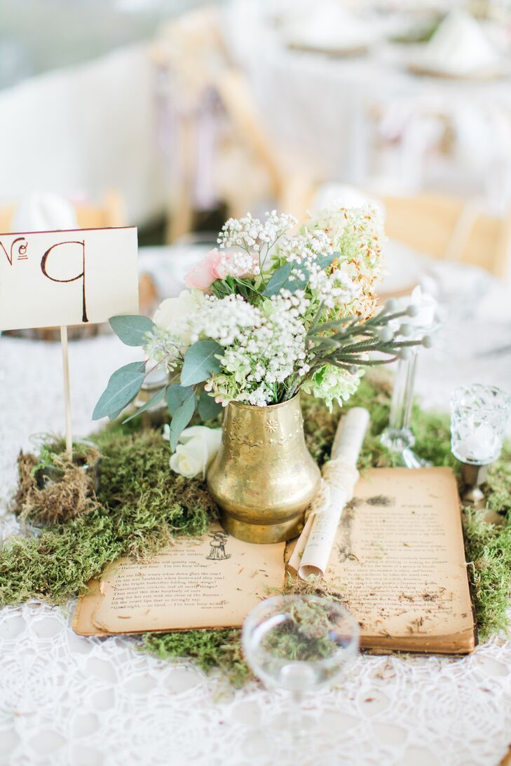 A vintage book, rolled-up sheet music and gold bud vases came together to create a whimsical centerpiece arranged on top of a bed of moss.