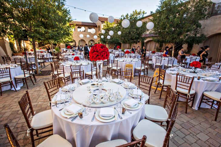 The reception took place outside on the terrace at Serra Plaza in San Juan Capistrano, California. Round dining tables were covered with white tablecloths and set with matching dinnerware. Tall and short centerpieces filled with red roses decorated the tables, positioned underneath hanging paper lanterns and string lights.