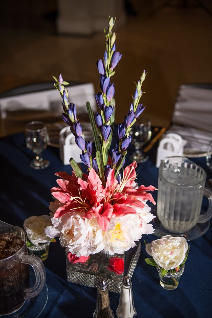 The couple incorporated their coral and navy color palette with colorful centerpieces and opted for silk flowers because peonies weren't in season.