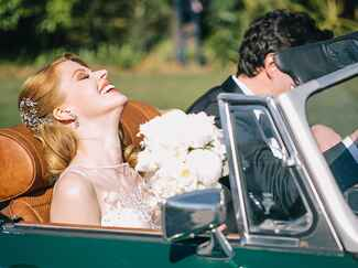 Bride and groom driving away from wedding
