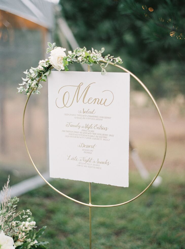 Hanging embroidery hoops, decorated with flowers and greenery, is a creative way to display the menu.