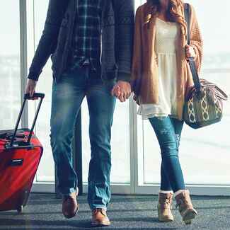 couple holding hands walking in airport