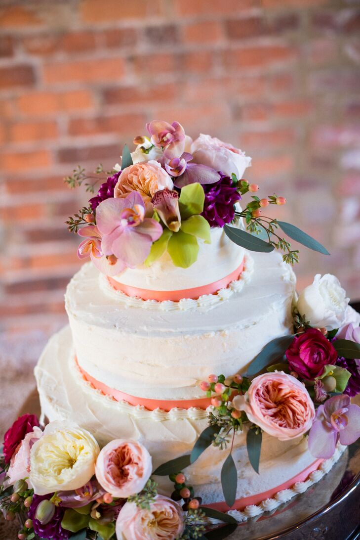 """Among the many beautiful reception tablescapes, our cake tables stood out as two focal points that reflected our true personalities,"" Emily says. The wedding cake was a three-tier pound cake with peach and blackberry-raspberry filling and draped with full, fresh flowers and garden greenery."