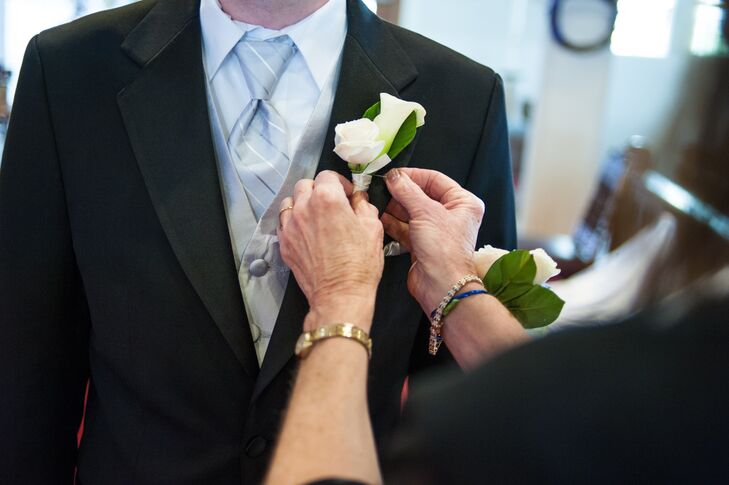 Leonard had an ivory rose and calla lily boutonniere pinned to his black tuxedo jacket.