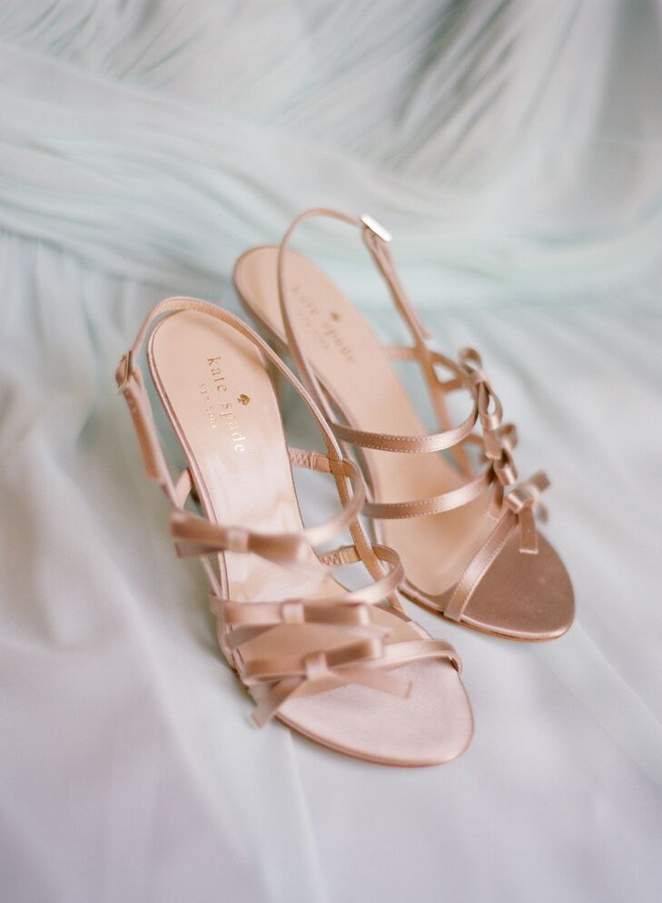 "Andrea completed her look with strappy gold Kate Spade shoes with three bows up the side. She loved that the shoes complemented the simplicity of her dress, but also added a little glamorous flair. ""Every girl needs a touch of Kate in her wedding,"" she says."
