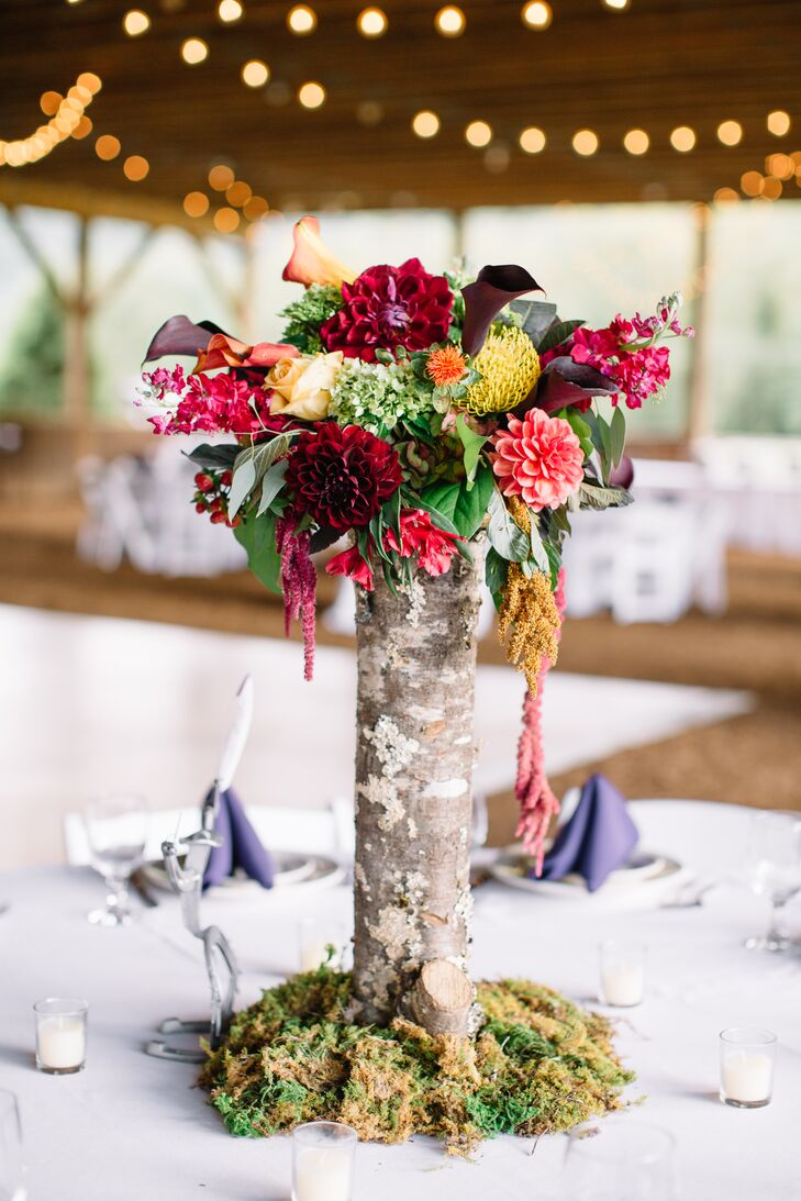 Rustic wood log centerpiece with green moss