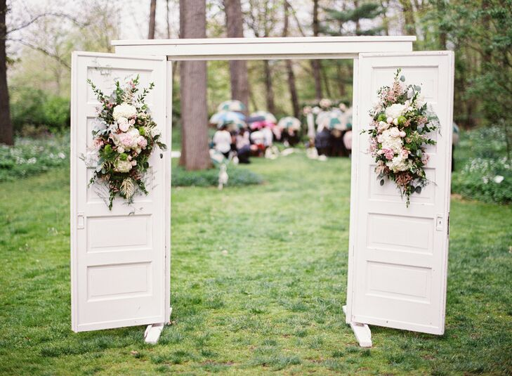 A set of vintage doors adorned in floral arrangements welcomed guests to the outdoor ceremony.