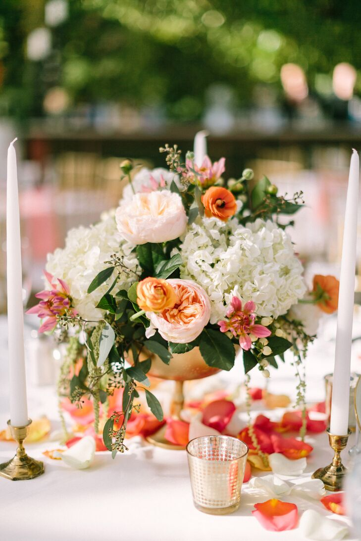 Golden urn centerpieces held pink, coral and ivory flowers.
