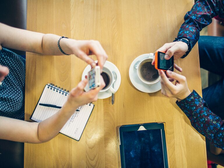 Couple looking at separate phones while they drink coffee in the morning.