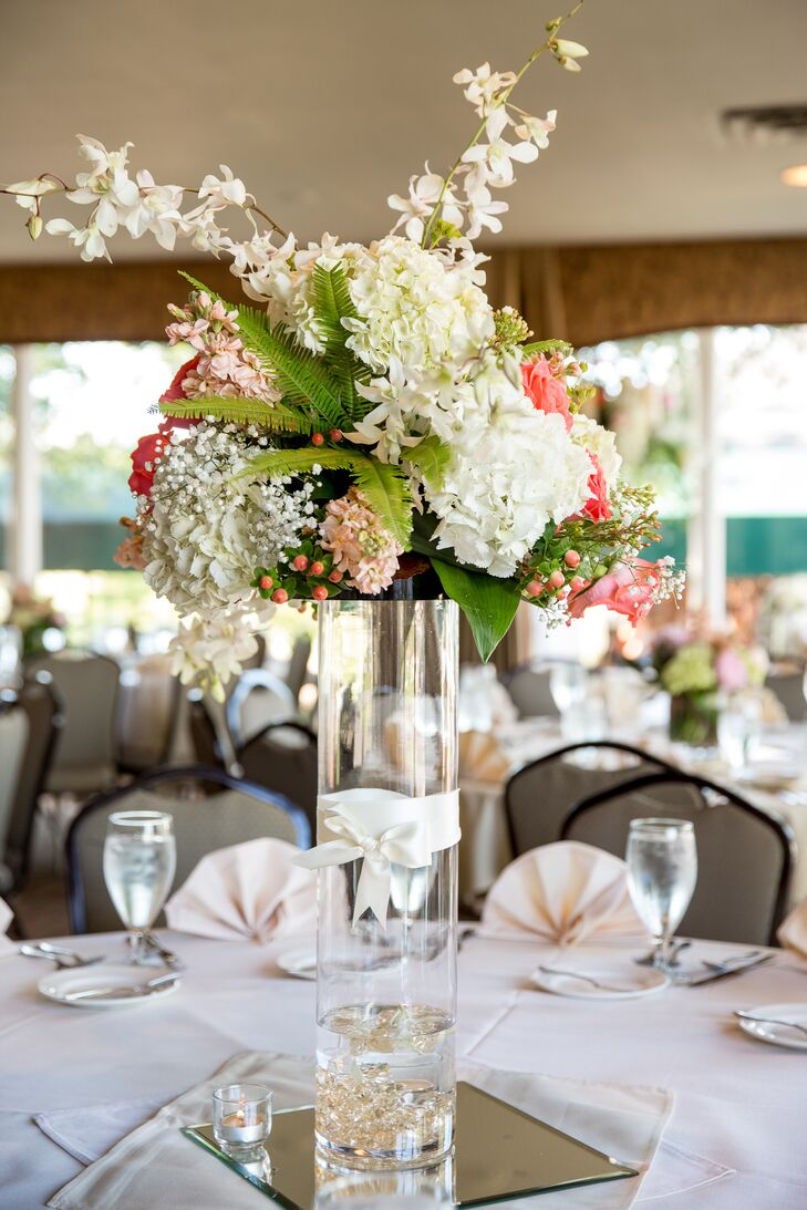Palmer Flowers created beautiful high centerpieces including hydrangeas, hypericum berries, baby's breath and ferns on top of round glass cylinders. The lush arrangements brought the outside in to the country club venue.